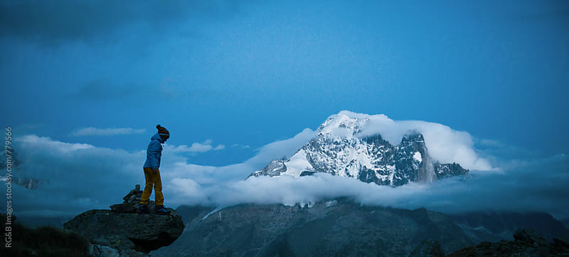 Woman standing on a high cliff with mountain peaks in the background by RG&B Images for Stocksy United