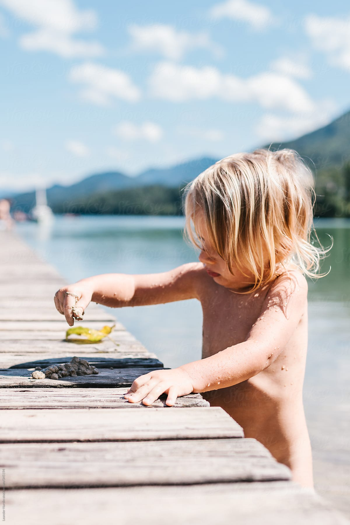 Naked Toddler Playing With Wet Sand On A Jetty At The Lake