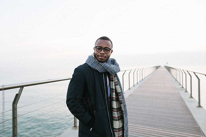 Portrait of an african american man standing on bridge over sea. by BONNINSTUDIO for Stocksy United