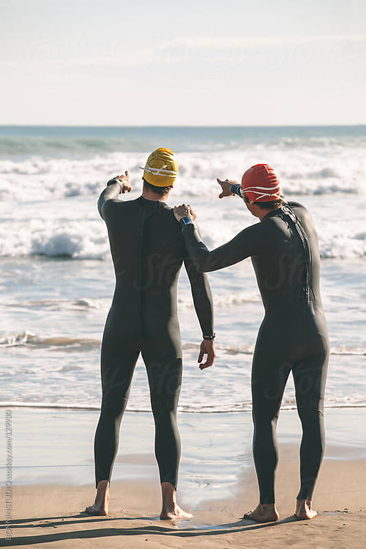 Two triathletes with wetsuit, cap and glasses pointing to the sea. by BONNINSTUDIO for Stocksy United
