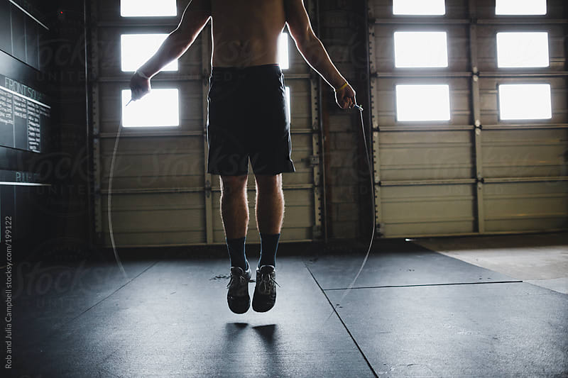 Young, fit man skipping rope - double unders - in gym by Rob and Julia Campbell for Stocksy United