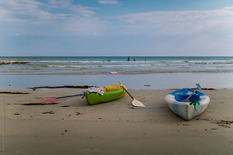 Kayaks left on summer beach by Rowena Naylor for Stocksy United