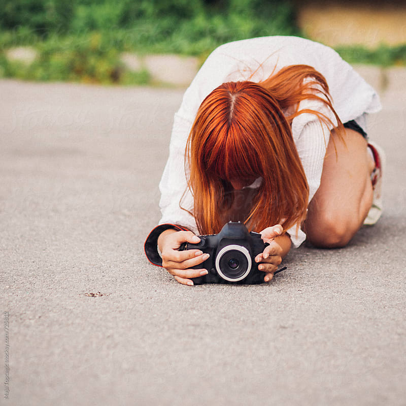 Woman with red hair taking photos from the ground by Maja Topcagic for Stocksy United