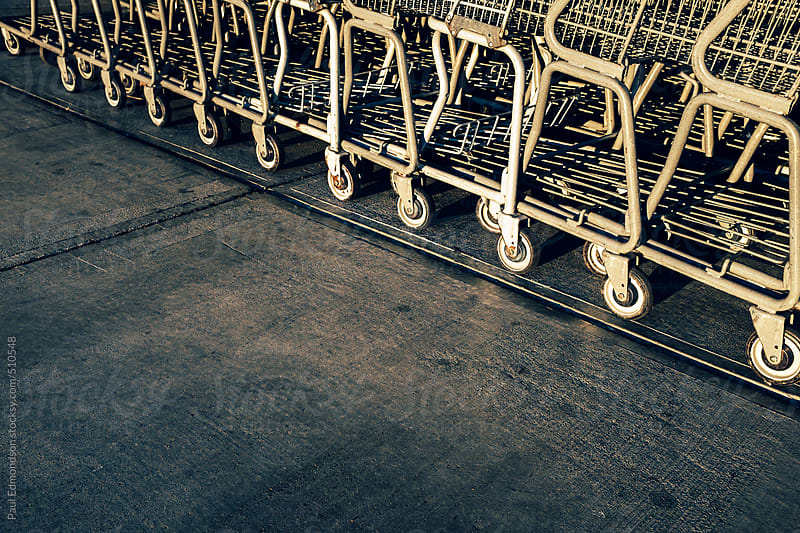 Metal grocery carts lined up on sidewalk outside supermarket by Paul Edmondson for Stocksy United