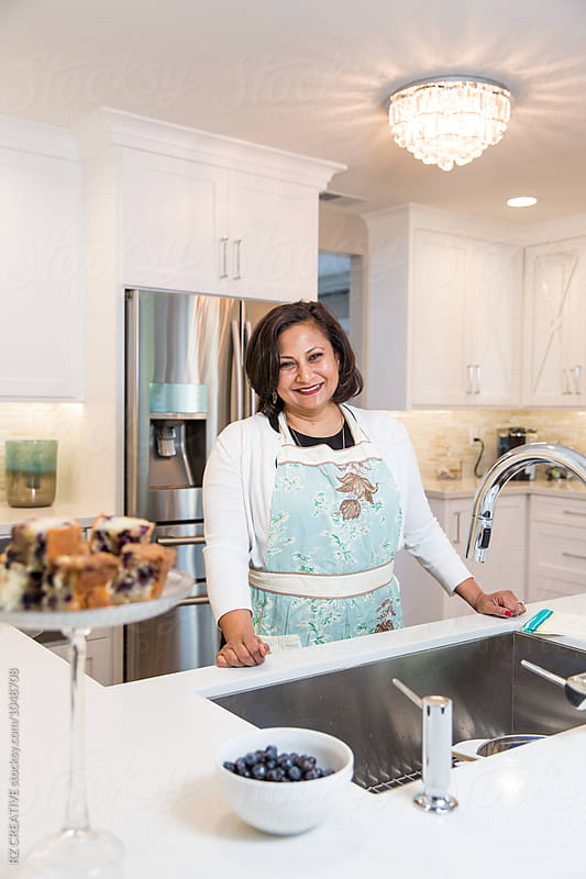 Portrait of East Indian woman at home in modern kitchen. by Robert Zaleski for Stocksy United