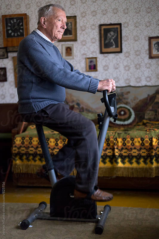 Old gentleman exercising insede his home by Jovana Milanko for Stocksy United