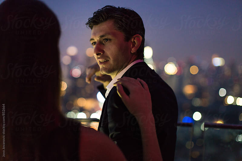Handsome man looking over his shoulder to his beautiful date in a modern rooftop lounge  by Jovo Jovanovic for Stocksy United