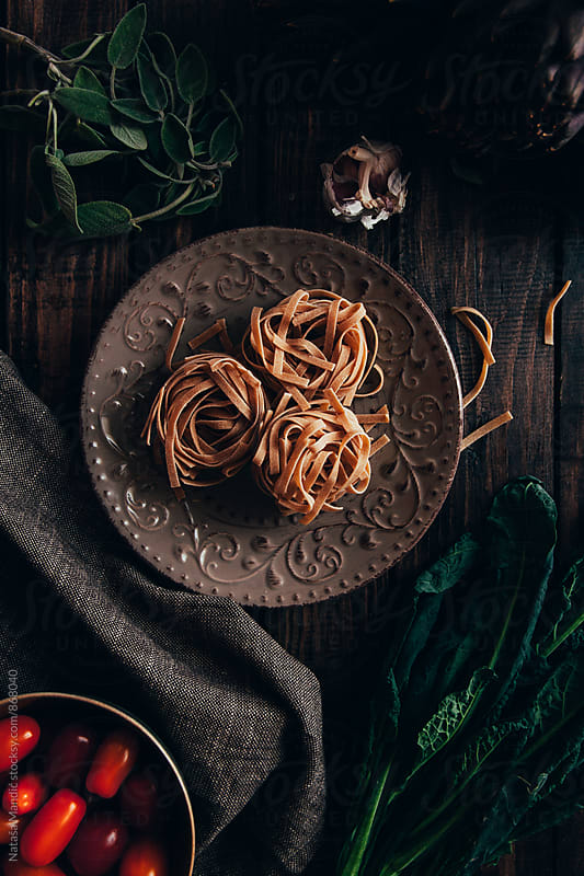 Raw pasta in a plate on dark background by Nataša Mandić for Stocksy United