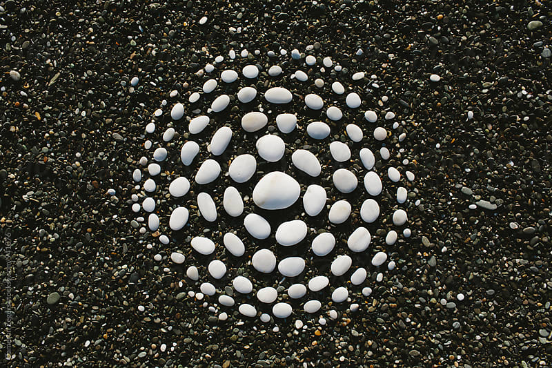 white stones arranged in circular pattern on beach by Cameron Zegers for Stocksy United