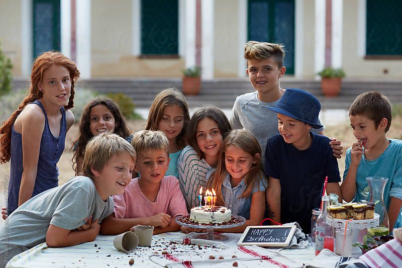 Group of children gathered around a birthday cake by Miquel Llonch for Stocksy United