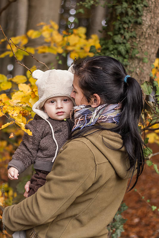 mother with her baby in colorful autumn forest by Leander Nardin for Stocksy United