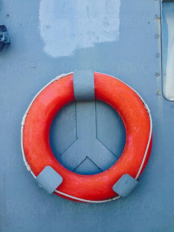 Life belt hanging on grey wall on ferry by Borislav Zhuykov for Stocksy United