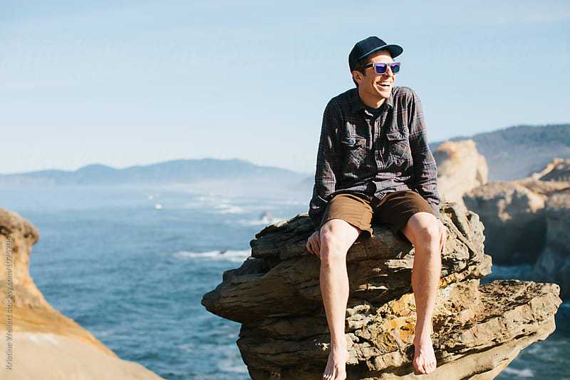 Man sitting on a rock with the ocean in the background by We Are SISU for Stocksy United