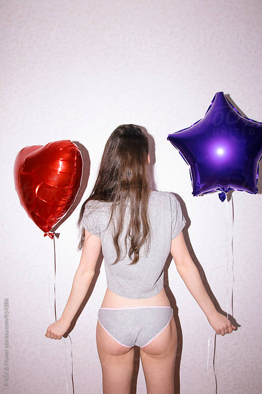 Back view of young woman in pants and t-shirt holding two balloons by Danil Nevsky for Stocksy United