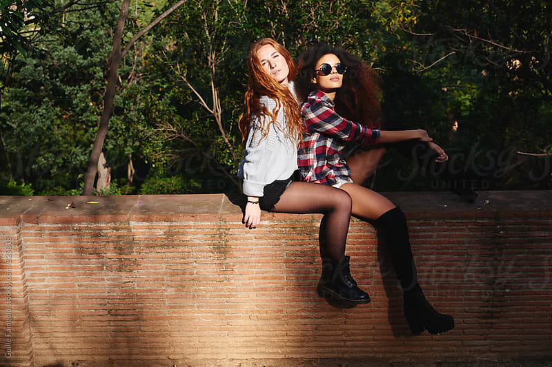 Two young women sitting on fence in park by Guille Faingold for Stocksy United