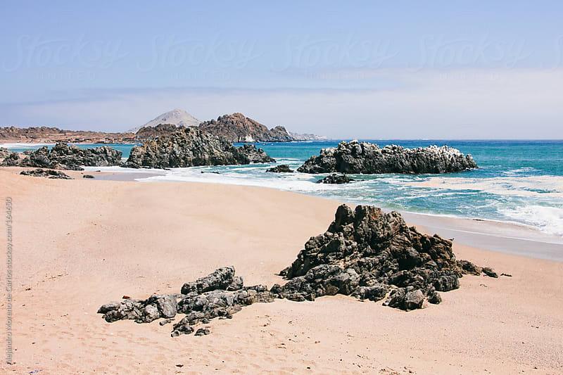 Beach with rocks and blue sea by Alejandro Moreno de Carlos for Stocksy United