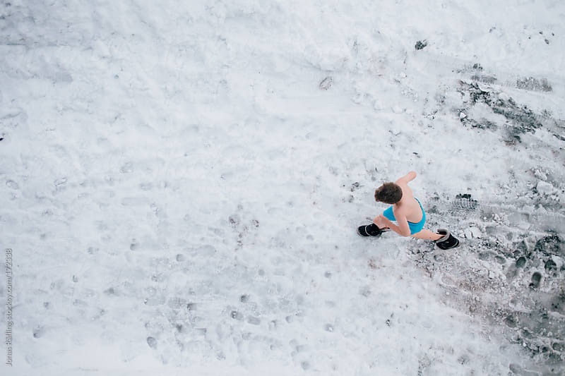 Boy running in the snow with only shorts and shoes from the sauna by Jonas Räfling for Stocksy United