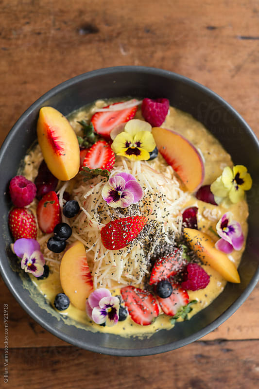 porridge covered with yummy things like seasonal fruits, nuts and seeds, focus on the fruit by Gillian Vann for Stocksy United