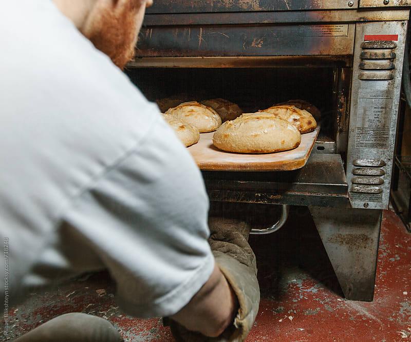 Baker pulling out freshly baked bread at a commercial artisinal bakery by Mihael Blikshteyn for Stocksy United