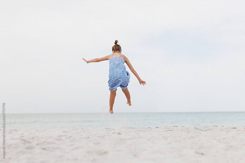 Girl jumping into air on the beach by Amanda Worrall for Stocksy United