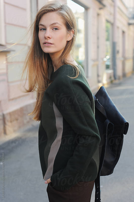 Portrait of young woman standing on the street by Liubov Burakova for Stocksy United