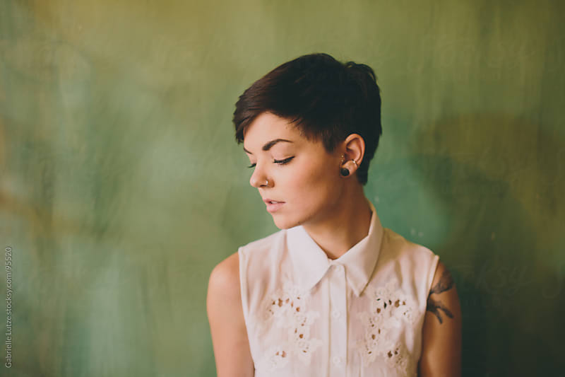 Girl with short hair in front of green wall by Gabrielle Lutze for Stocksy United