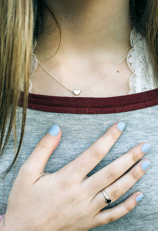 Teenage girl with long hair - hand to her chest and a silver heart necklace by Carolyn Lagattuta for Stocksy United