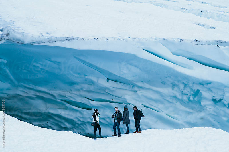 4 people standing outside ice cave by Jesse Morrow for Stocksy United
