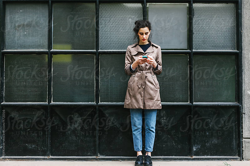 Fashionable woman browsing on her mobile phone by Marija Kovac for Stocksy United