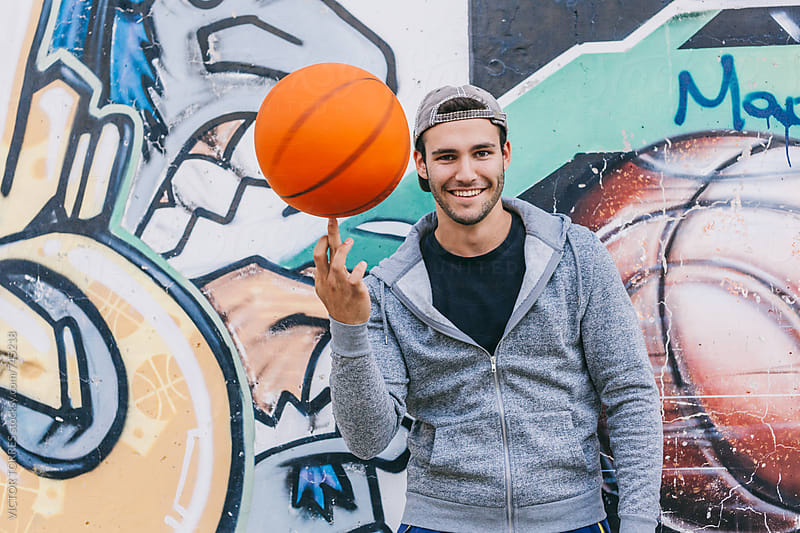 Young Happy Man Showing His Skills with a Basket Ball by Victor Torres for Stocksy United
