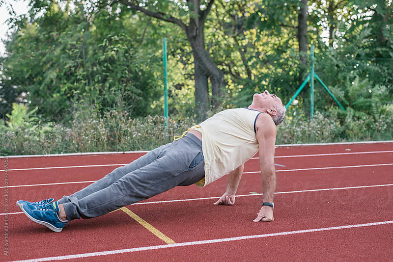 Middle-aged Man Doing Exercise on the Racetrack by Aleksandra Jankovic for Stocksy United