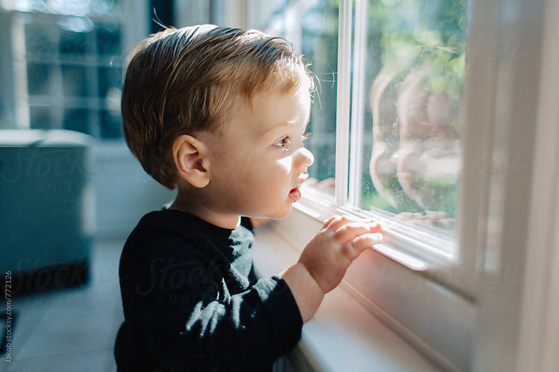 Cute toddler boy looking out a window by Jakob for Stocksy United