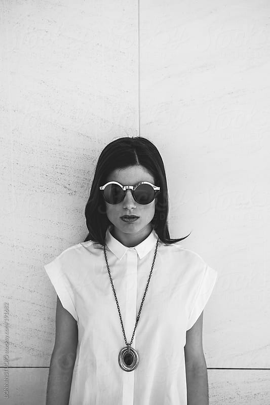 Portrait of stilish fashion woman wearing round sunglasses and black necklace.  by BONNINSTUDIO for Stocksy United