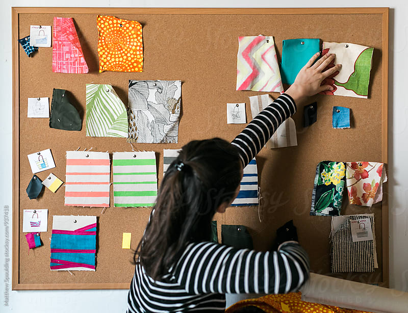 Woman designer arranging sample patterns on cork board by Matthew Spaulding for Stocksy United