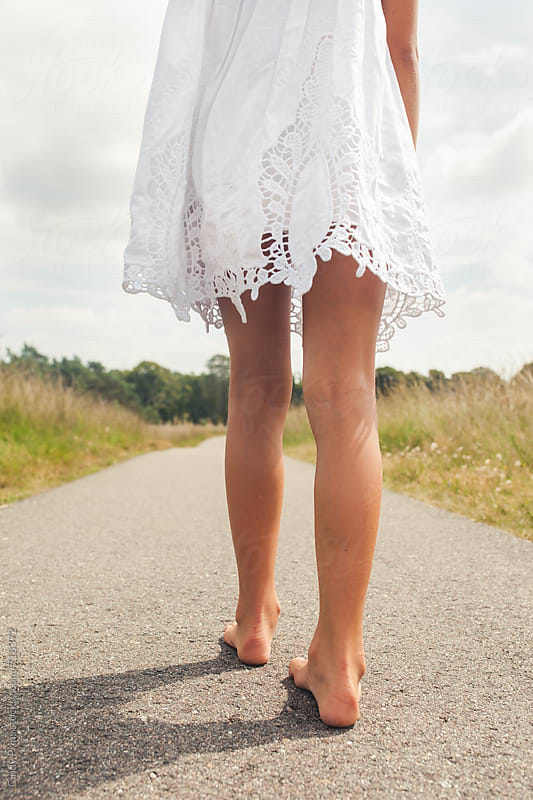 Bare feet and legs of a little girl in a white dress by Cindy Prins for Stocksy United