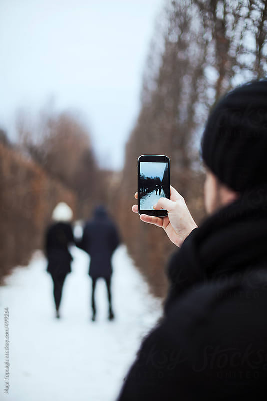 Man taking a photo of a young couple kissing in the city park at winter by Maja Topcagic for Stocksy United