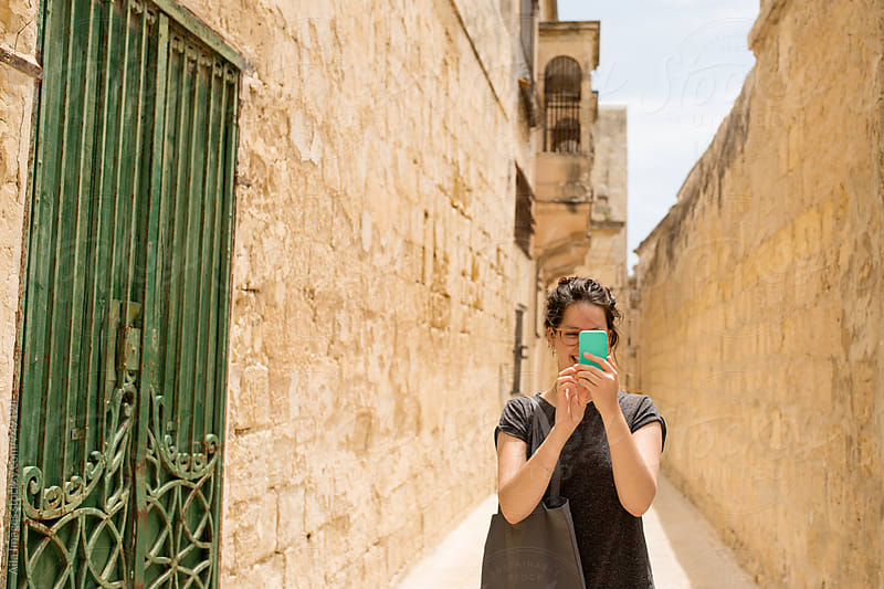Tourist exploring old city with smart phone by Aila Images for Stocksy United
