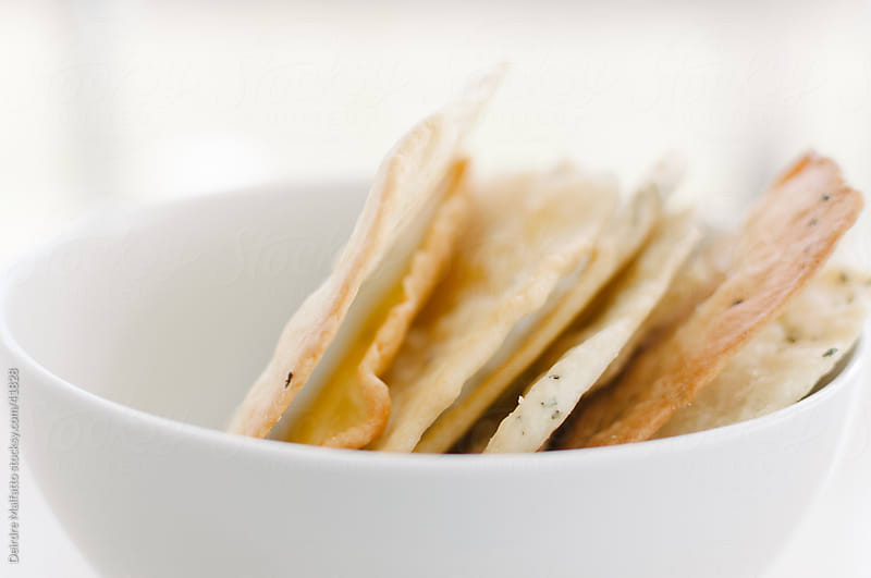 A bowl of homemade flatbread crackers by Deirdre Malfatto for Stocksy United