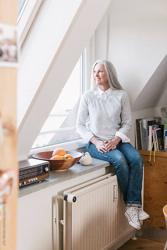 Portrait of a beautiful senior woman, sitting on a windowsill. by Lilly Bloom for Stocksy United