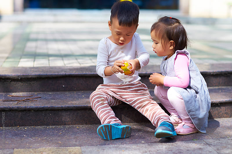 little asian girl waiting to eat fruit by Bo Bo for Stocksy United