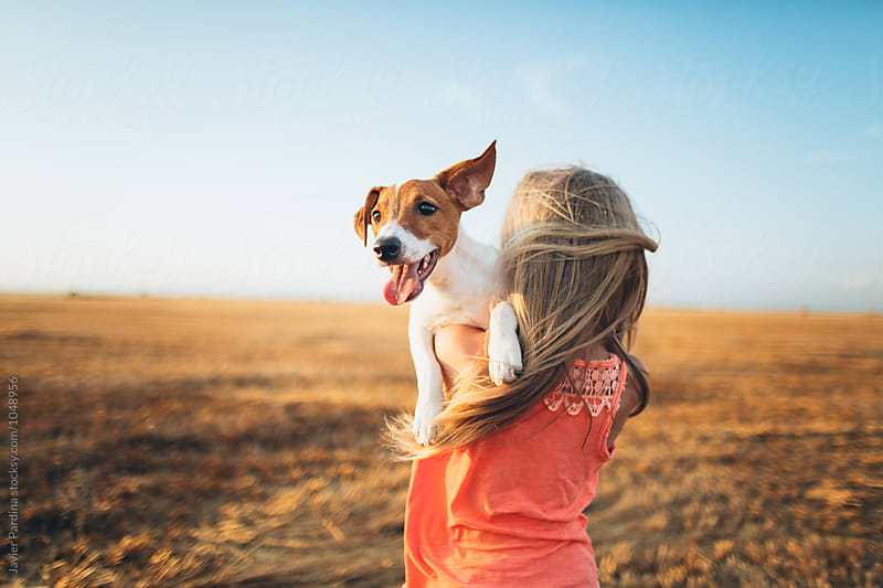 child playing with puppy at sunset  by Javier Pardina for Stocksy United