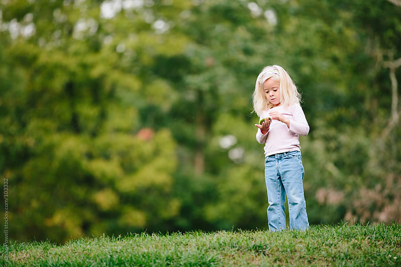 girl inspecting moss she found by Brian Powell for Stocksy United