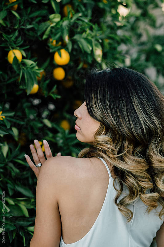 Profile portrait of a woman in front of an orange tree by ZOA PHOTO for Stocksy United