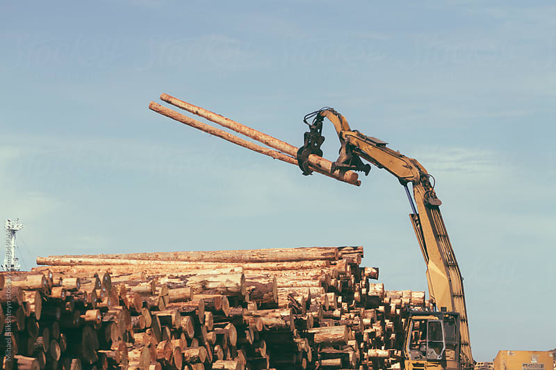 Vintage view of a timber log grabber piling up tree logs by Mihael Blikshteyn for Stocksy United