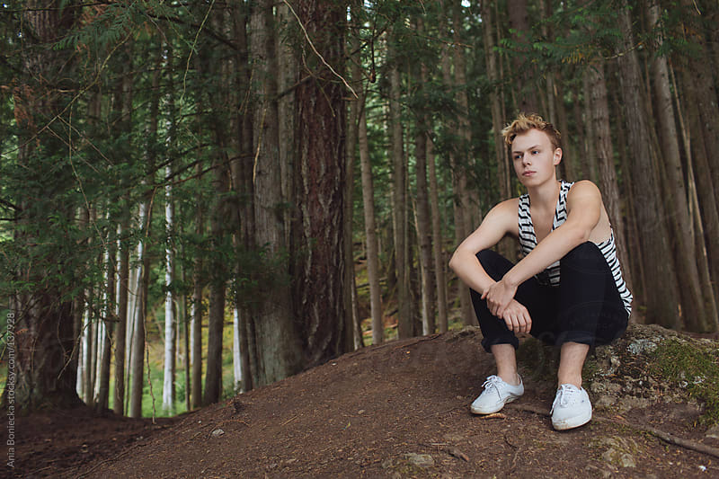 A handsome young man sitting on a forest floor by Ania Boniecka for Stocksy United