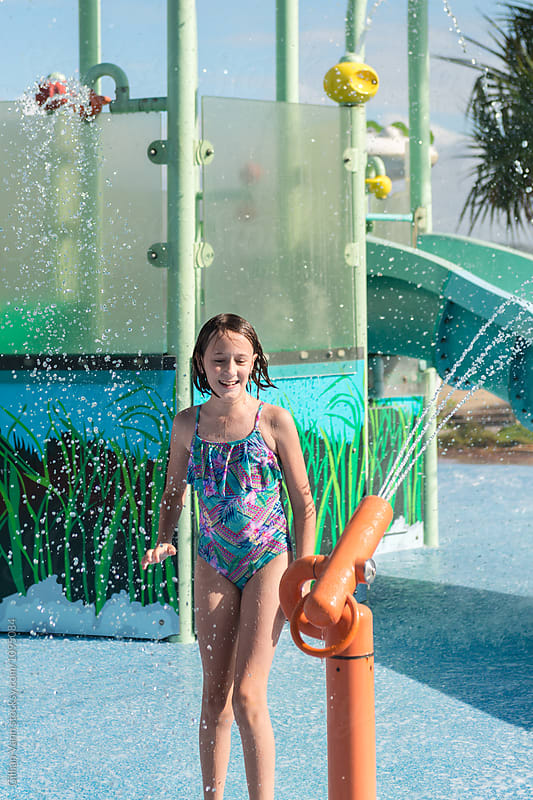 girl having fun at a waterpark   by Gillian Vann for Stocksy United