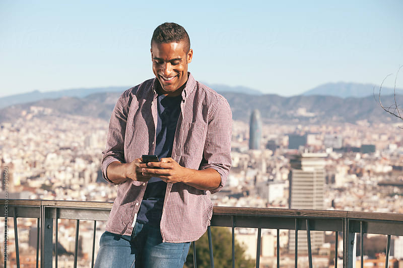 Black young man using mobile phone on nice panorama of Barcelona.  by BONNINSTUDIO for Stocksy United
