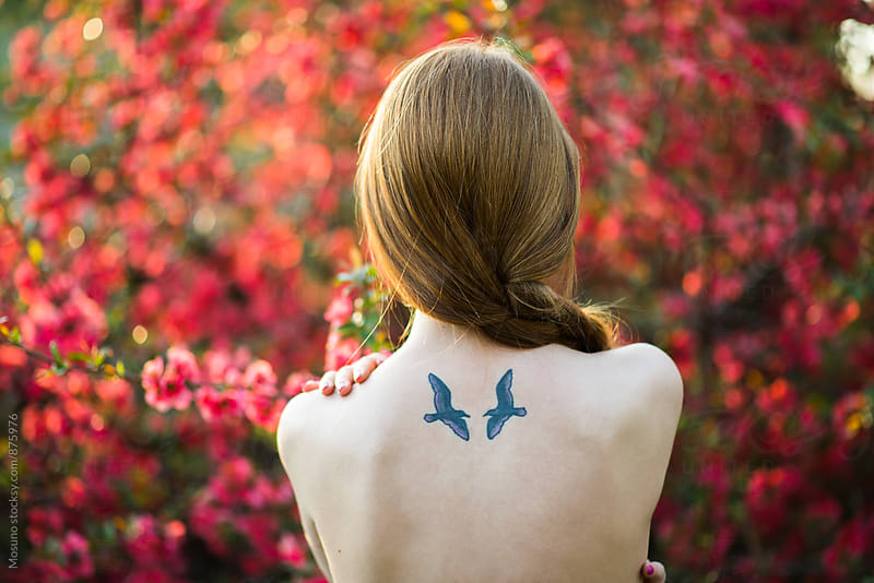 Woman With Bird Tattoo in a Spring Garden by Mosuno for Stocksy United