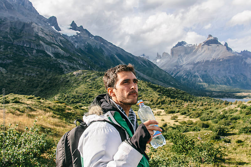 Young man drinking water and hiking on the mountains of Torres del Paine, Chile, Patagonia by Alejandro Moreno de Carlos for Stocksy United