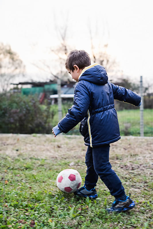 Young boy playing soccer by Mauro Grigollo for Stocksy United